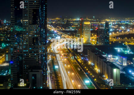 Dubai at night looking East along Sheikh Zayed Road from Emirates Towers Metro Station - Stock Photo
