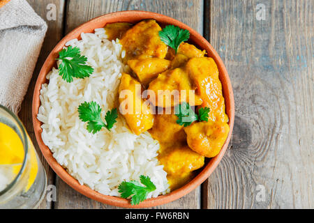 chicken curry with rice on a wooden surface - Stock Photo