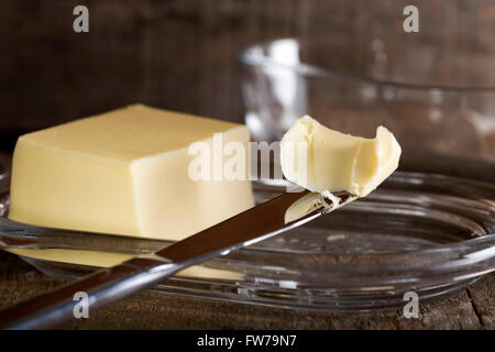 Knife with butter and butter dish in background - Stock Photo