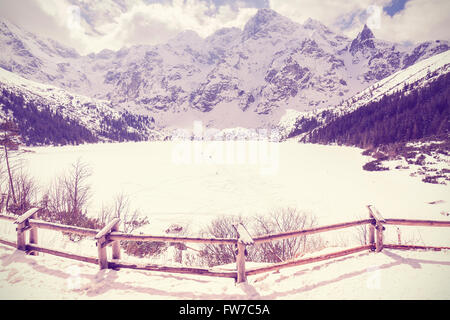 Vintage stylized frozen lake Morskie Oko in Tatra Mountains, most popular mountain lake in Poland. - Stock Photo