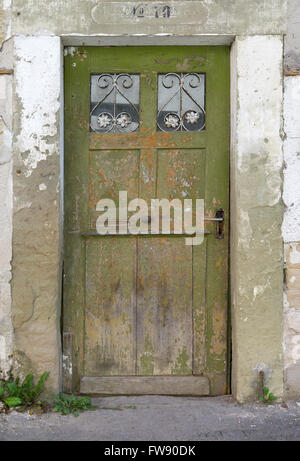 Old, green, weathered wooden door with two small barred glass panes in the dilapidated facade of an abandoned house. - Stock Photo