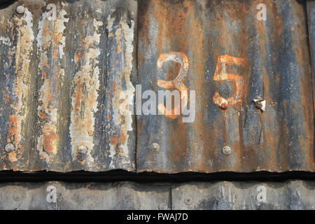 35; number thirty-five painted on old rusty corrugated sheet metal - Stock Photo