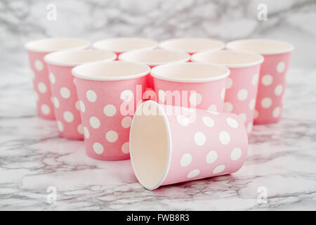 Group of pink  disposable paper cups on white marble background - Stock Photo