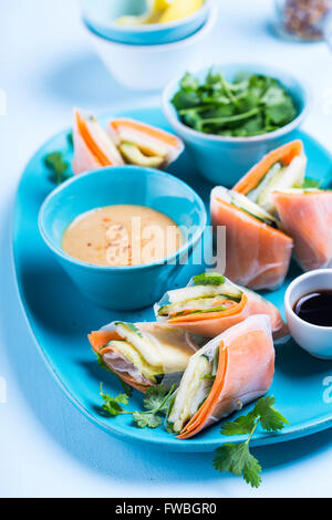 Fresh spring rolls served on a plate with different sauces - Stock Photo