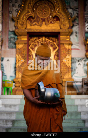 Thai Monk recieving morning alms - Stock Photo