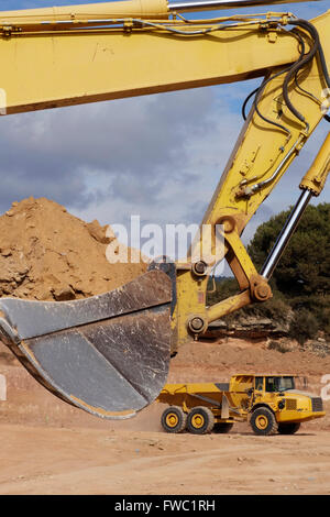 Heavy excavator and truck, working in a large excavation - Stock Photo