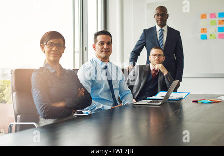 Four confident successful multiracial diverse business partners or associates seated at a boardroom table having - Stock Photo
