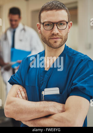 Serious confident young surgeon wearing glasses and surgical scrubs standing in a hospital with folded arms looking - Stock Photo