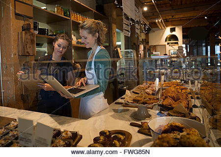 Bakery owner and worker with laptop and clipboard - Stock Photo