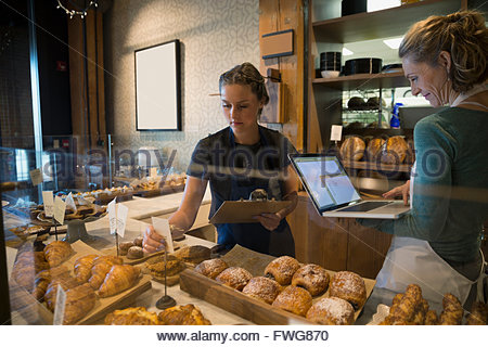 Bakery owner and worker with laptop taking inventory - Stock Photo