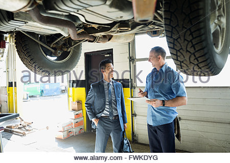 Mechanic and customer talking in auto repair shop - Stock Photo