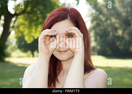 Portrait Of Young Woman Peering Through Hands In Park - Stock Photo