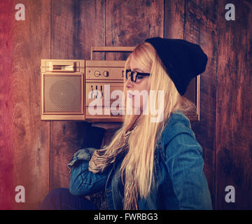 A hipster girl with glasses is listening to a vintage gold boombox radio with a speaker for a music entertainment - Stock Photo