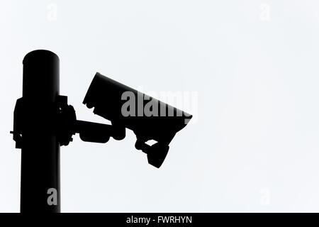 Silhouette of a CCTV camera on a pole. - Stock Photo