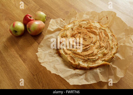 Freshly baked apple pie on baking paper with apples lying next to it - Stock Photo