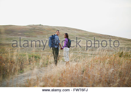 Couple holding hands as they walk through a field. - Stock Photo