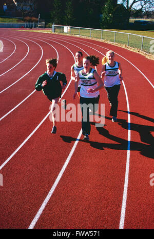 High school girls track team running on synthetic surface outdoor track - Stock Photo