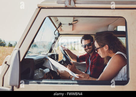 Man and woman on a road trip and reading a map together while seated inside their car. Happy young couple going - Stock Photo