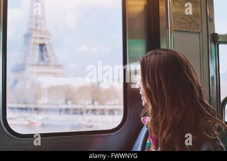 tourist looking to the Eiffel Tower through the window of metro in Paris, smiling girl visiting France - Stock Photo