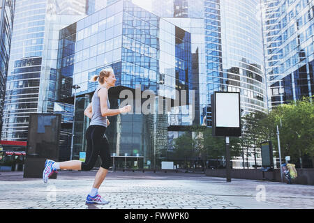 young woman running on urban background - Stock Photo