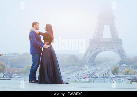 happy couple traveling in Paris, smiling man and woman posing in fancy fashion clothes on Eiffel Tower background - Stock Photo