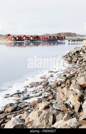 Sweden, Bohuslan, Orust, Edshultshall, Wooden houses and rocky coastline in winter - Stock Photo