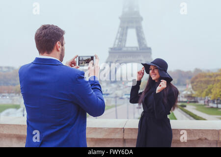 mobile photography, man taking photo of woman with his phone, couple of tourists near Eiffel Tower in Paris, France - Stock Photo