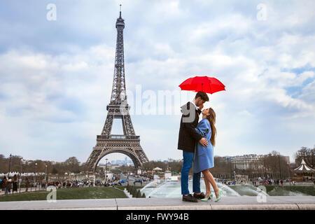 beautiful couple with umbrella near Eiffel Tower, honeymoon in Paris, romantic moment - Stock Photo