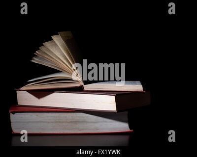 Old hardback books. Unidentifiable texts. Reflected on shiny black background - Stock Photo
