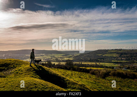Little Solsbury Hill, Batheaston, Somerset, UK . A dog walker  admires the view from the top of the old Iron Age - Stock Photo