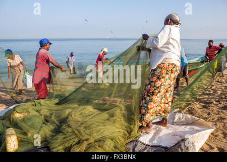 People repairing fishing nets amidst their colorful fishing boats at Negombo Beach, Sri Lanka - Stock Photo