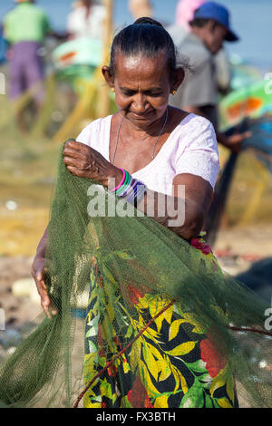 People repairing fishing nets amidst their colorful fishing boats at Negombo Beach, Sri Lanka - Stock Photo