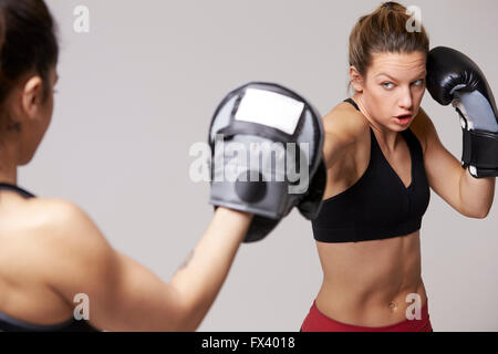 Front view of female boxer punching mitt of sparring partner - Stock Photo