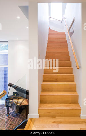 Wooden staircase leading to the upper terrace and grand piano mezzanine. Avenue Road Residence, Ottawa, Canada. - Stock Photo