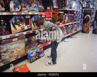 Young boy looking at Star Wars toys in a toy store - Stock Photo
