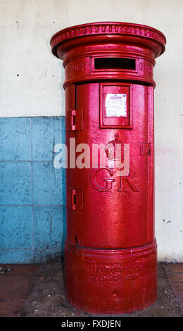 Photo of GR Royal Mail red post box against dirty wall - Stock Photo