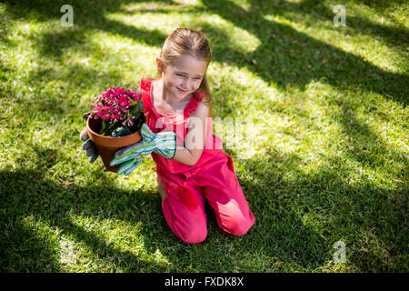 Girl holding flower pot while sitting in yard - Stock Photo
