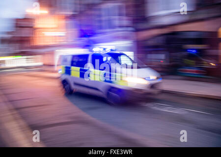 999 emergency services: a police vehicle with blue lights flashing, speeding to an incident along a city street - Stock Photo