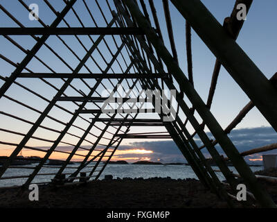 Silhouette of rack for drying stockfish at sunset, near Henningsvaer on Lofoten Islands, Norway - Stock Photo
