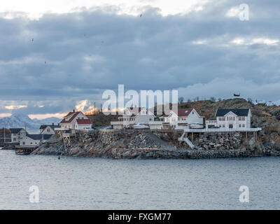 Clouds at sunset over houses in Henningsvaer on Austvagoy, Lofoten Islands, northern Norway, Scandinavia - Stock Photo