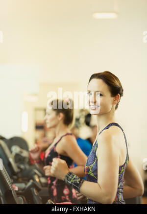 Portrait smiling woman jogging on treadmill at gym - Stock Photo