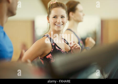 Smiling woman jogging on treadmill at gym - Stock Photo