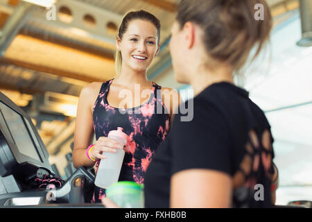 Smiling women talking and drinking water at gym - Stock Photo
