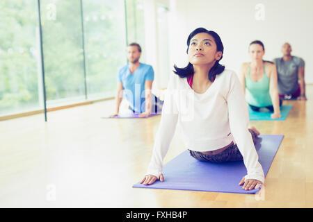 Woman in upward facing dog position in yoga class - Stock Photo