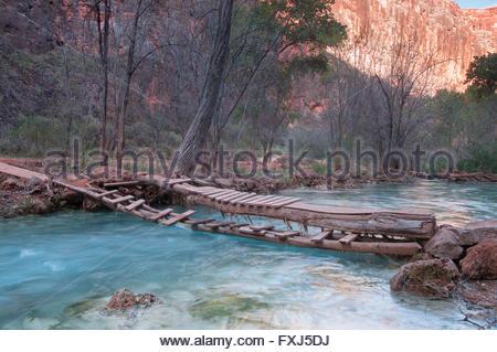 Little wooden bridge over mountain river - Stock Photo