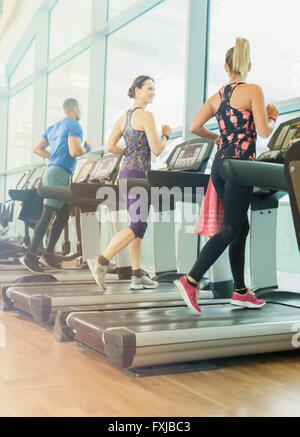 Man and women jogging on treadmills at gym - Stock Photo
