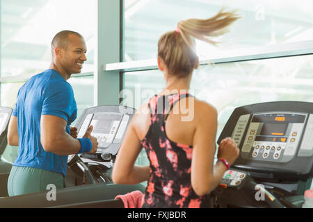 Man and woman talking and running on treadmills at gym - Stock Photo