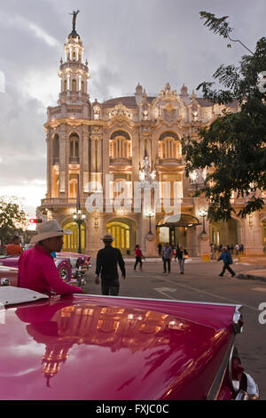 Vertical view of classic American cars parked outside the Grand Theatre at sunset in Havana, Cuba. - Stock Photo