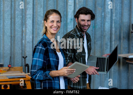 Happy carpenters holding digital tablet and laptop - Stock Photo