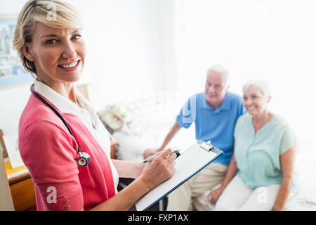 Nurse writing on clipboard and senior couple sitting on a bed - Stock Photo